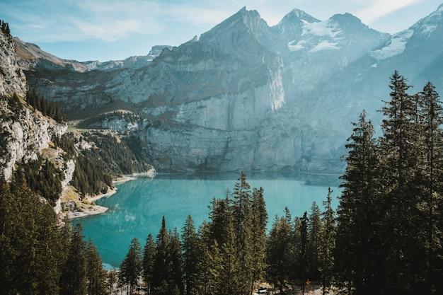Lago cercado por rochas cobertas de neve e florestas sob o sol Foto gratuita