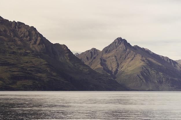Lago cercado por rochas sob o sol na nova zelândia Foto gratuita