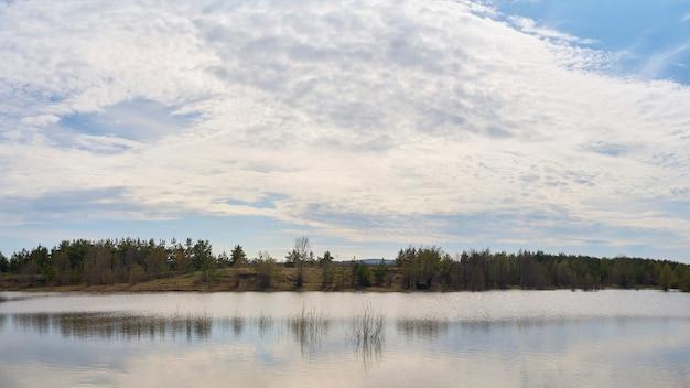 Lago com belas nuvens e floresta em um dia ensolarado. Foto Premium