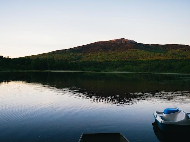 Lago tranquilo no sopé de uma montanha contra um céu brilhante Foto gratuita
