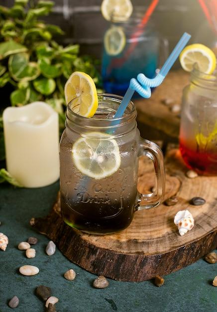 Lagoa azul, vermelho e marrom cocktail com fatias de limão dentro do frasco com vara Foto gratuita