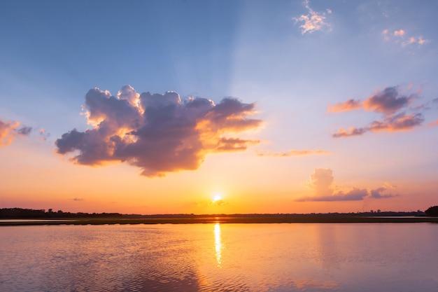 Lagoa de reflexão do sol. belo pôr do sol por trás das nuvens e céu azul acima da paisagem sobre a lagoa Foto Premium