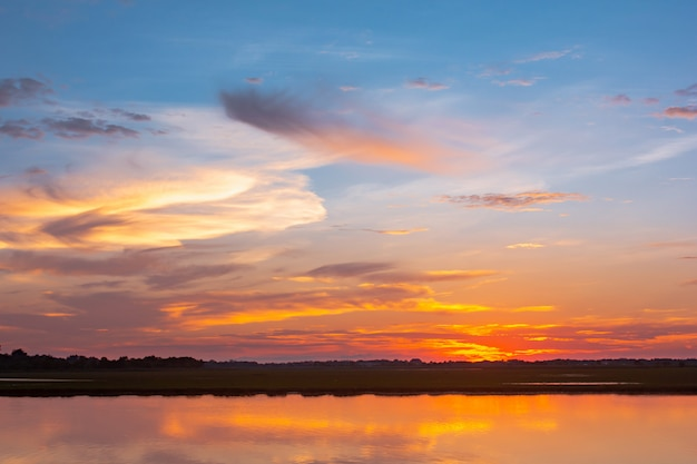 Lagoa de reflexão do sol. por do sol bonito atrás das nuvens e do céu azul acima da paisagem excedente da lagoa. céu dramático com nuvem ao pôr do sol Foto Premium