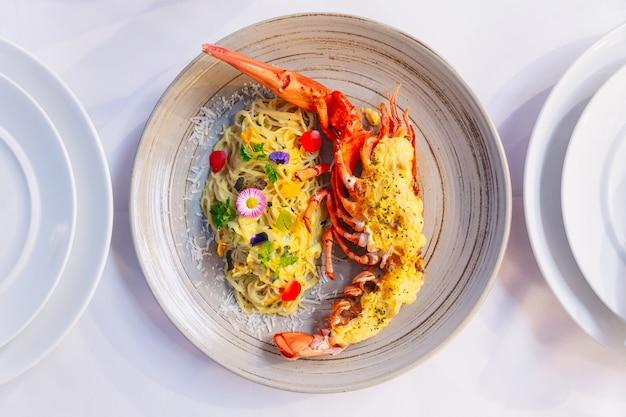 Lagosta cozida com queijo servido com espaguete carbonara decorado com flores e pétalas. Foto Premium