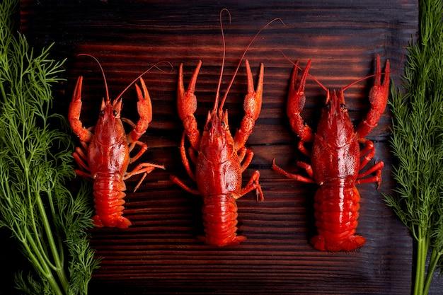 Lagosta cozida lagostins cozida pronta para comer no fundo escuro de madeira Foto Premium