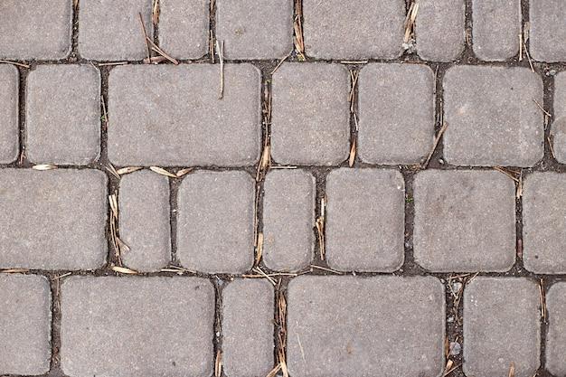 Lajes ou pedras de pavimento cinza de calçada ou concreto para piso, parede ou caminho. pavimentação de cerca, quadra, quintal ou estrada tradicional. Foto Premium