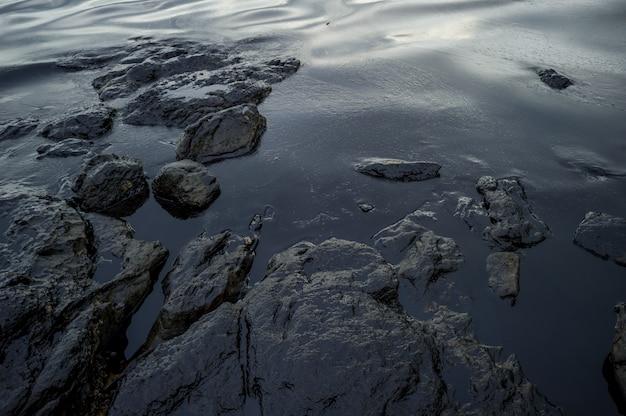 Lama de petróleo que contamina o mar durante o desastre do derramamento de óleo na ilha de samet, rayong, tailândia. Foto Premium