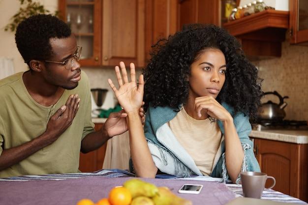 Lamentável infeliz jovem afro-americano de óculos tentando falar gentilmente com sua esposa ofendida que está sentada ao lado dele na mesa da cozinha, recusando todas as suas mentiras. pessoas e relacionamentos Foto gratuita