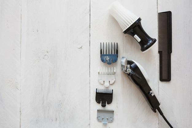 Lâmina de cabeleireiro perto de escova e pente Foto gratuita