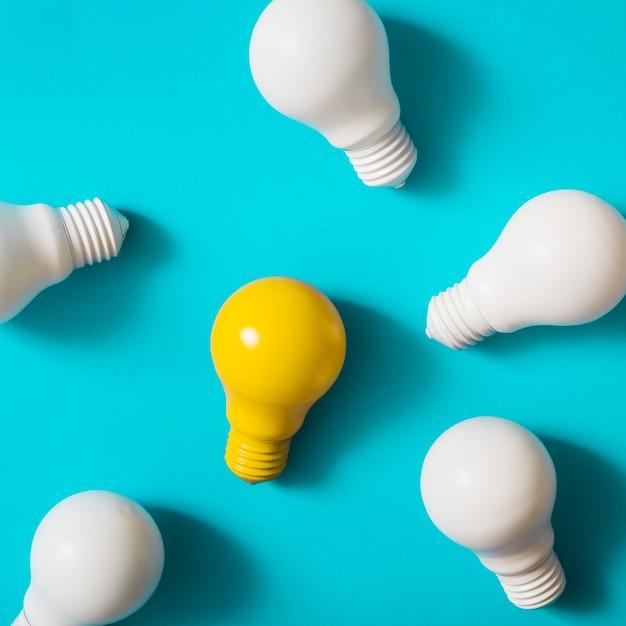 Lâmpada amarela entre as lâmpadas brancas sobre fundo azul Foto Premium