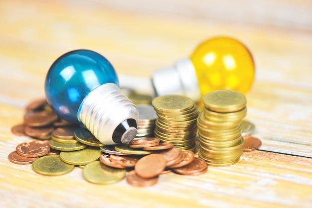 Lâmpada com luz da lâmpada em moedas empilhadas em um fundo de mesa de madeira - idéia de economia de energia, economia de energia e o conceito de mundo Foto Premium
