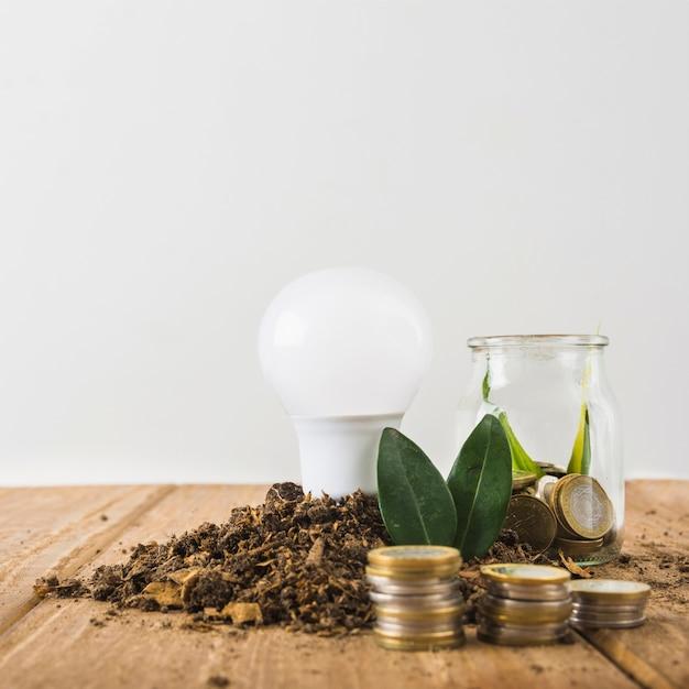 Lâmpada com pilhas de jarra e moedas de vidro Foto gratuita