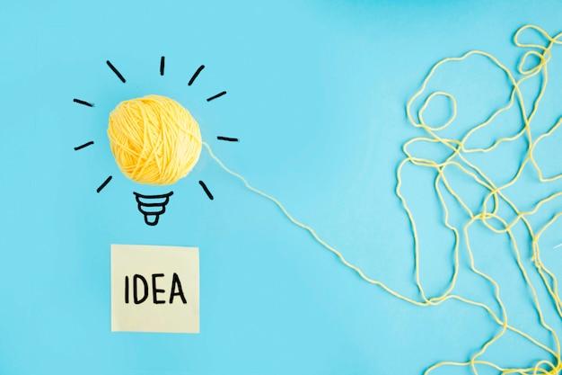 Lâmpada de ideia de lã amarela sobre fundo azul com texto de ideia na nota auto-adesiva Foto gratuita
