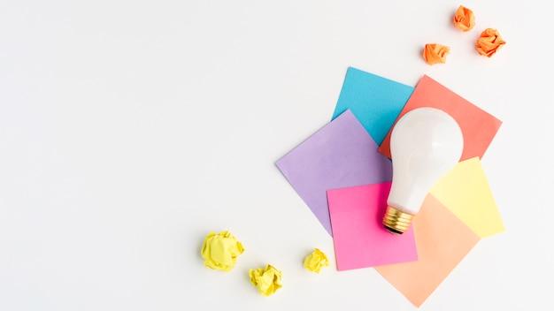 Lâmpada de luz branca na nota adesiva colorida com papel amassado amarelo Foto gratuita