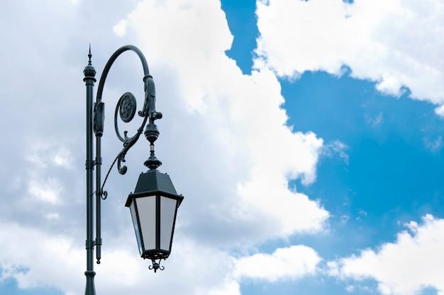 Lâmpada de rua antiga contra um céu azul com nuvens. Foto Premium