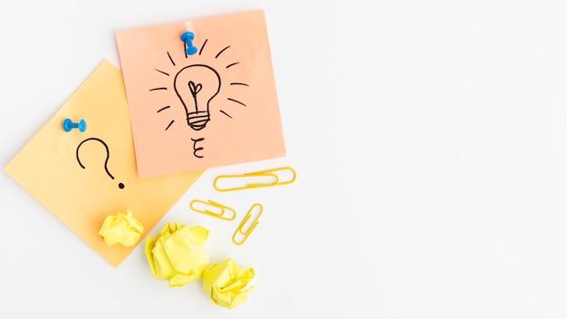 Lâmpada desenhada e sinal de interrogação na nota adesiva anexada com pino sobre fundo branco Foto gratuita