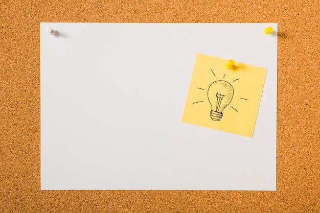 Lâmpada desenhada ícone na nota auto-adesiva amarela sobre o quadro de avisos Foto gratuita