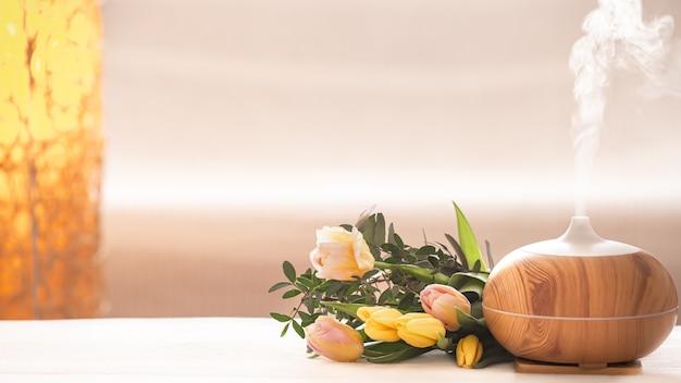 Lâmpada difusor de óleo de aroma em cima da mesa em um fundo desfocado com um lindo buquê de tulipas primavera. Foto gratuita