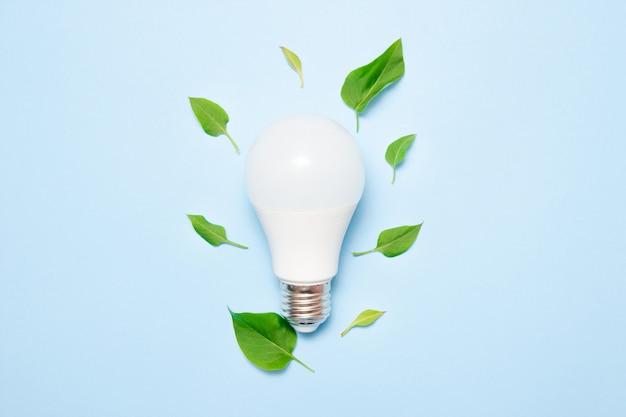 Lâmpada led com folhas em um fundo azul Foto Premium