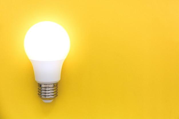 Lâmpada led no fundo amarelo, conceito de idéias, criatividade, inovação ou economia de energia, cópia espaço, vista superior, lay plana Foto Premium