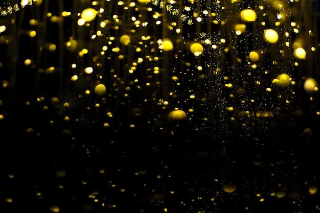 Lâmpada pendurada num candelabro, iluminando um pequeno bokeh de ouro amarelo Foto Premium