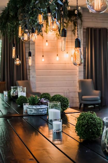 Lâmpadas de garland of edison penduradas em atacadores, decoradas por galhos de flores verdes. efeito granulado Foto Premium