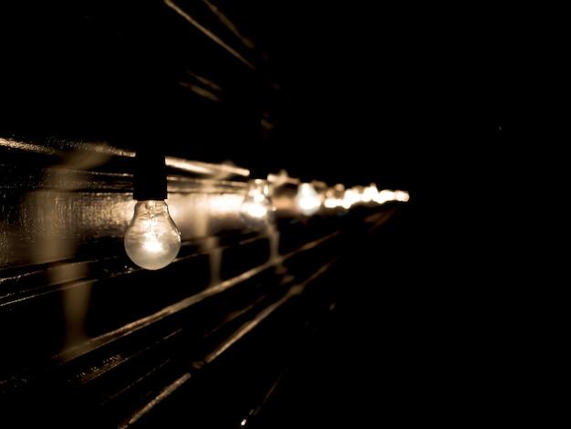 Lâmpadas em fundo preto. luz turva e bokeh. magia de ano novo e natal Foto Premium