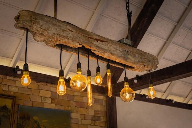 Lâmpadas incandescentes decorativas com madeira e contra o fundo da parede de tijolo Foto Premium