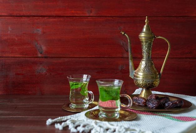 Lanche close-up de datas na placa de vidro com mentha chá no fundo Foto Premium