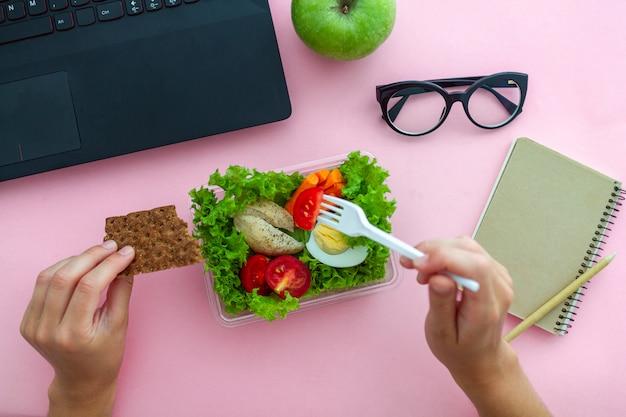 Lanche saudável da lancheira no local de trabalho durante a hora do almoço no escritório. recipiente de alimentos no trabalho. vista do topo Foto Premium