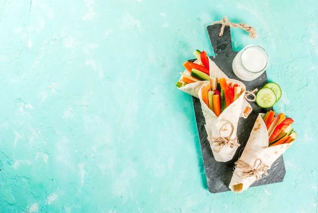 Lanche saudável de verão, sanduíche de tortilha de estilo mexicano envolve sortidas varas coloridas de legumes frescos (aipo, ruibarbo, pimenta, pepino e cenoura) com molho de iogurte mergulham fundo azul claro Foto Premium