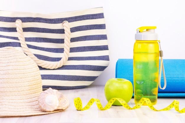 Lanche saudável, fita métrica e garrafa de água sobre uma superfície de madeira clara. preparação para a temporada de verão e a praia, bolsa de praia, chapéu e conchas, perda de peso e conceito de esportes Foto Premium