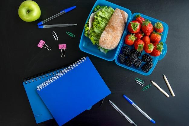 Lancheira, cadernos e papelaria na mesa Foto gratuita