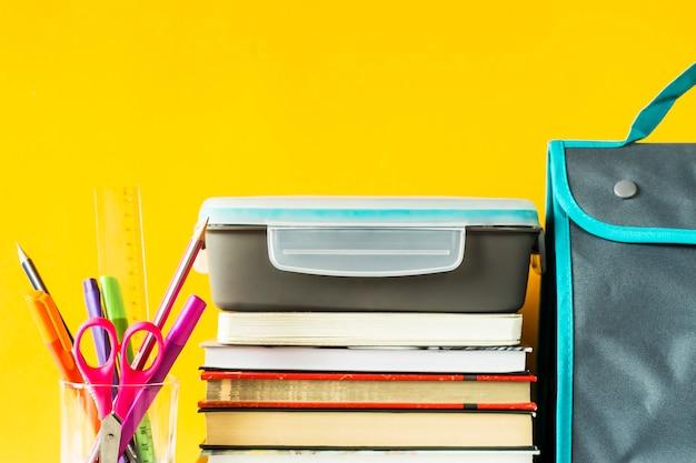 Lancheira com comida fica em uma pilha de rei ao lado de um copo com canetas e lápis e um saco para o almoço Foto Premium
