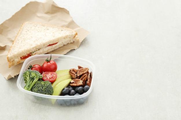 Lancheira com comida saudável e sanduíche Foto gratuita