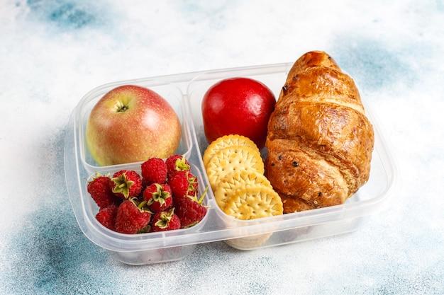 Lancheira com croissant fresquinho, biscoitos, frutas e framboesas. Foto gratuita