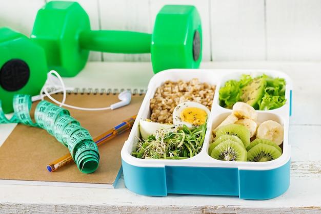 Lancheira com ovos cozidos, aveia, abacate, verduras e frutas. comida saudável de fitness. leve embora. lancheira. Foto Premium