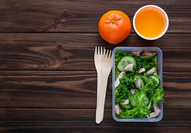 Lancheira com salada, maçã, tangerina e suco. Foto Premium