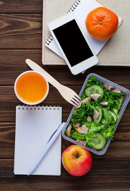 Lancheira com salada, notebook e telefone Foto Premium