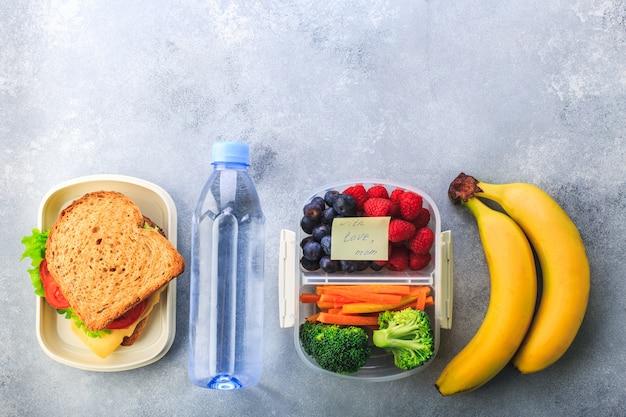 Lancheira com sanduíche bagas cenoura brócolis garrafa de banana água na cinza Foto Premium