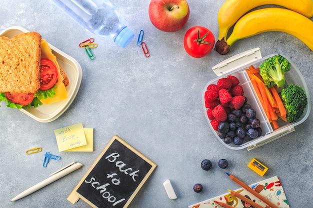 Lancheira com sanduíche bagas cenoura brócolis garrafa de banana água na vista superior cinza Foto Premium
