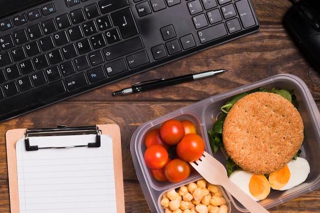 Lancheira de vista superior e teclado com caderno em branco Foto gratuita