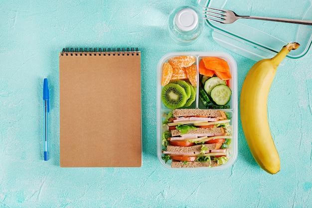 Lancheira escolar com sanduíche, legumes, água e frutas na mesa. Foto Premium