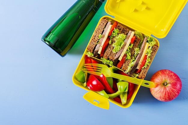 Lancheira escolar saudável com sanduíche de carne e legumes frescos, garrafa de água e frutas na mesa azul. vista do topo. configuração plana Foto gratuita