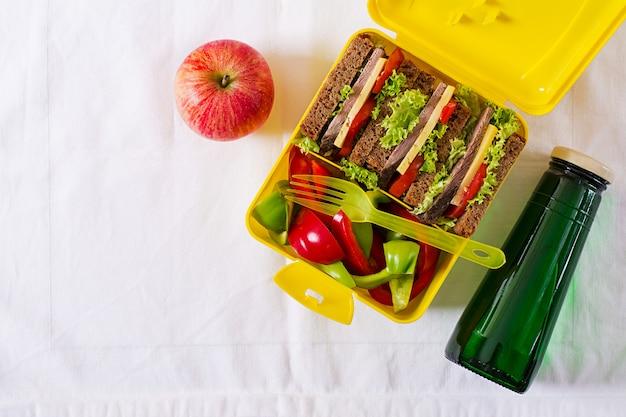 Lancheira escolar saudável com sanduíche de carne e legumes frescos, garrafa de água e frutas na mesa branca. vista do topo. configuração plana Foto gratuita