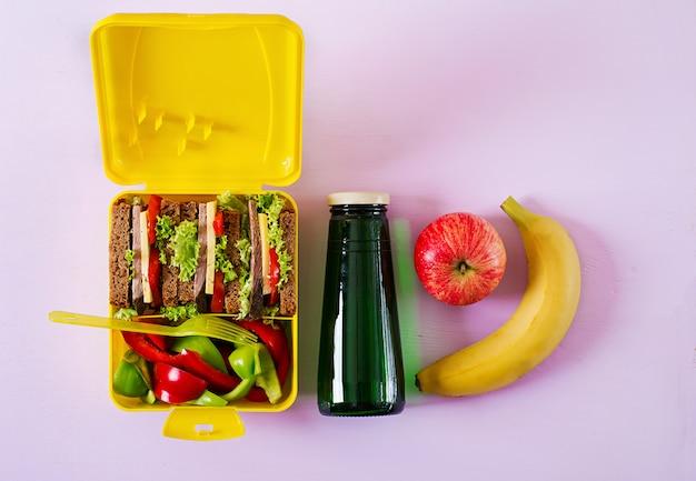 Lancheira escolar saudável com sanduíche de carne e legumes frescos, garrafa de água e frutas na superfície rosa Foto Premium