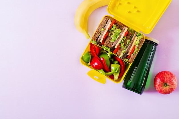 Lancheira escolar saudável com sanduíche de carne e legumes frescos, garrafa de água e frutas no fundo rosa Foto Premium
