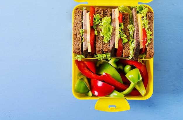 Lancheira escolar saudável com sanduíche de carne e legumes frescos, garrafa de água e frutas Foto Premium
