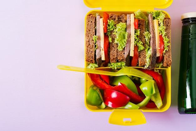 Lancheira escolar saudável com sanduíche de carne e legumes frescos, garrafa de água na mesa-de-rosa. vista do topo. configuração plana Foto gratuita