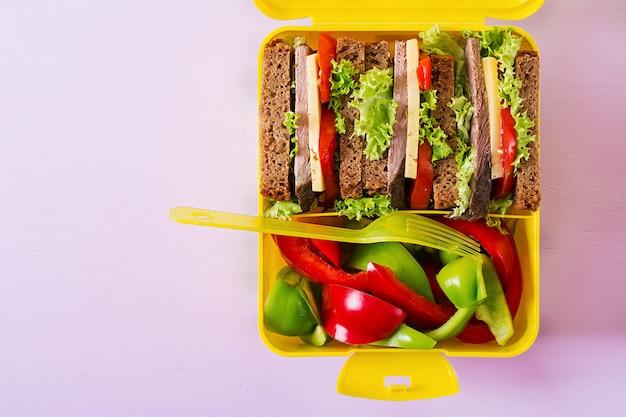 Lancheira escolar saudável com sanduíche de carne e legumes frescos na mesa-de-rosa. vista do topo. configuração plana Foto gratuita